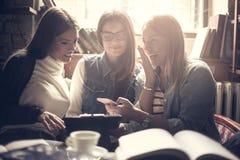 Ragazze colpite smiley che utilizzano cellulare nel caffè Immagine Stock