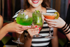 Ragazze con i cocktail che tostano contro i colori di volo fotografia stock libera da diritti