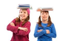 Ragazze con i libri sulla testa Immagine Stock