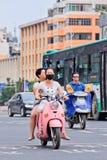 Ragazze con il cappuccio su una e-bici, Kinming, Cina della bocca Fotografie Stock