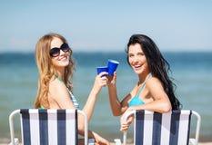 Ragazze con le bevande sulle sedie di spiaggia Immagine Stock Libera da Diritti