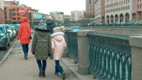 Ragazze con le mamme che camminano sull'argine della città sul fondo urbano di architettura stock footage