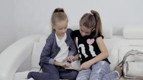 Ragazze con un ridurre in pani Un ritratto di due amici femminili all'interno Due adolescenti che esaminano il pc della compressa stock footage