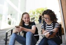 Ragazze degli studenti che si siedono sulla scala Fotografie Stock