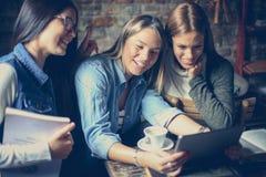 Ragazze degli studenti che utilizzano iPod nel caffè Fotografia Stock