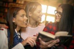 Ragazze degli studenti nel libro di lettura delle biblioteche e in conversa avere Immagini Stock Libere da Diritti
