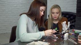 Ragazze dei clienti che scelgono un colore per i suoi chiodi video d archivio