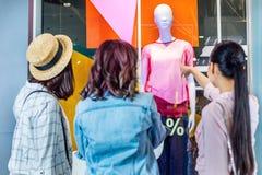 Ragazze dei pantaloni a vita bassa che esaminano vetrina nel centro commerciale, concetto di compera degli amici Immagini Stock