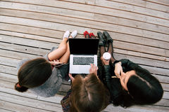 ragazze dei pantaloni a vita bassa che guardano qualcosa sul NET-libro portatile con lo schermo in bianco dello spazio della copi Immagini Stock Libere da Diritti