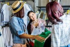 Ragazze dei pantaloni a vita bassa che scelgono i vestiti in boutique, concetto delle ragazze di acquisto di modo Immagini Stock