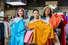 Ragazze dei pantaloni a vita bassa che scelgono i vestiti in boutique, concetto delle ragazze di acquisto di modo Fotografia Stock Libera da Diritti
