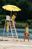 Ragazze del bagnino che si siedono sulla sedia con l'ombrello davanti al lago Fotografie Stock