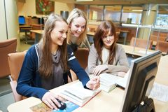 Ragazze dell'allievo che lavorano con il calcolatore in libreria Fotografia Stock