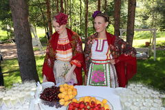 Ragazze dell'ospite di riunione belle in costumi russi nazionali, prendisole degli abiti con ricamo vibrante - gruppo piega la ru Fotografia Stock Libera da Diritti