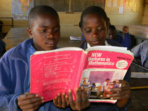 Ragazze della scuola primaria che leggono il manuale di matematica nella classe Immagine Stock