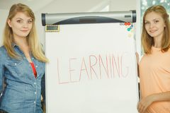 Ragazze dello studente che scrivono imparando parola sulla lavagna Immagini Stock Libere da Diritti