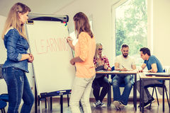 Ragazze dello studente che scrivono imparando parola sulla lavagna Immagine Stock Libera da Diritti