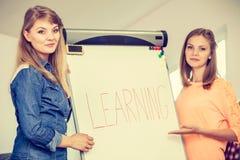Ragazze dello studente che scrivono imparando parola sulla lavagna Fotografie Stock