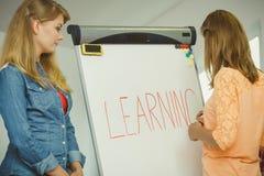 Ragazze dello studente che scrivono imparando parola sulla lavagna Fotografia Stock Libera da Diritti