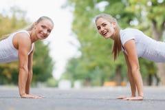 Ragazze di forma fisica che fanno spinta-UPS all'aperto su un fondo del parco Ragazze sportive Concetto di allenamento Copi lo sp Immagine Stock