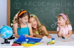 Ragazze di risata felici dell'allievo dei bambini al banco Immagini Stock