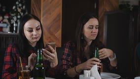 Ragazze divertenti della società che bevono birra e che parlano nella pizzeria stock footage