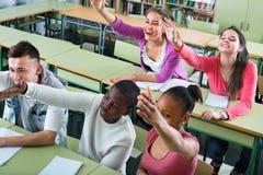 Ragazze e ragazzi che sollevano le loro mani nella classe Fotografie Stock Libere da Diritti