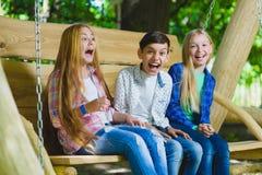 Ragazze e ragazzo sorridenti divertendosi al campo da giuoco Bambini che giocano all'aperto di estate Adolescenti su un'oscillazi Fotografie Stock