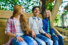 Ragazze e ragazzo sorridenti divertendosi al campo da giuoco Bambini che giocano all'aperto di estate Adolescenti su un'oscillazi Immagine Stock