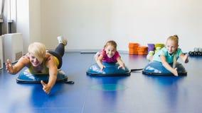 Ragazze ed istruttore o madre che fanno gli esercizi relativi alla ginnastica nella classe di forma fisica video d archivio