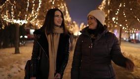 Ragazze felici che camminano lungo il vicolo di notte decorato dalla ghirlanda sugli alberi archivi video