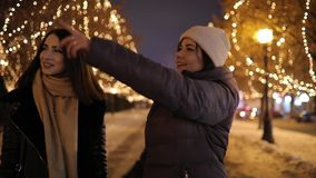 Ragazze felici che camminano lungo il vicolo di notte decorato dalla ghirlanda sugli alberi stock footage