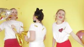 Ragazze felici che hanno partito e che ballano sul fondo giallo stock footage