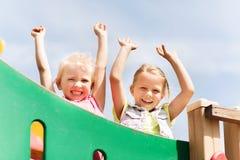Ragazze felici che ondeggiano le mani sul campo da giuoco dei bambini Fotografia Stock Libera da Diritti