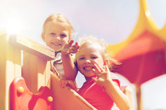 Ragazze felici che ondeggiano le mani sul campo da giuoco dei bambini Immagine Stock