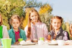 Ragazze felici che si siedono alla tavola fuori con le tazze Fotografia Stock