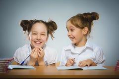 Ragazze felici che si siedono allo scrittorio sul fondo grigio Concetto del banco Fotografie Stock Libere da Diritti