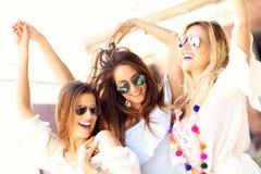 Ragazze felici che vanno in giro nella città di estate Immagine Stock