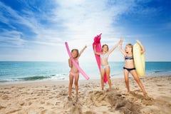 Ragazze felici con gli strumenti di nuoto sulla spiaggia sabbiosa Fotografie Stock