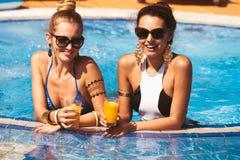 Ragazze felici con le bevande dallo stagno Fotografia Stock Libera da Diritti