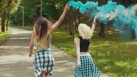 Ragazze felici dei pantaloni a vita bassa nei bei funzionamenti dei vestiti in parco che ondeggia fumo colorato archivi video