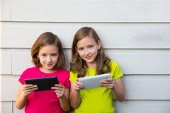 Ragazze gemellate della sorella che giocano con il pc della compressa felice sulla parete bianca Immagine Stock