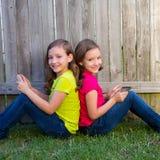 Ragazze gemellate della sorella che giocano il pc della compressa che si siede sul prato inglese del cortile Immagini Stock Libere da Diritti