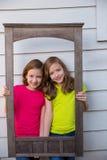 Ragazze gemellate della sorella che posano con la struttura di legno invecchiata del confine Fotografie Stock