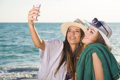 Ragazze graziose alla spiaggia che prende Selfie fotografia stock