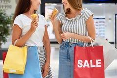 Ragazze graziose che comperano nel centro commerciale sulla vendita Fotografia Stock Libera da Diritti