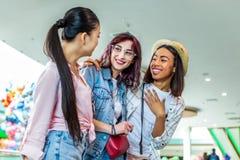 Ragazze multiculturali dei pantaloni a vita bassa nel centro commerciale, concetto di compera degli amici Immagine Stock