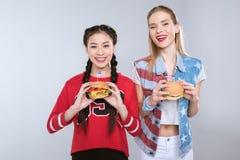 Ragazze multietniche sorridenti che tengono gli hamburger con le bandiere di U.S.A., celebrazione di festa dell'indipendenza Fotografia Stock