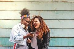 Ragazze multirazziali dell'adolescente facendo uso dell'aria aperta del telefono cellulare immagine stock libera da diritti