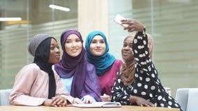 Ragazze multirazziali musulmane dello studente nei hijabs che prendono selfie al corridoio dell'università archivi video